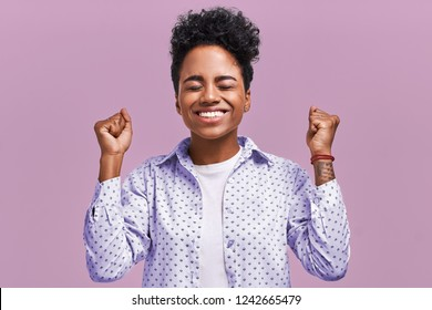Horizontal shot of happy mixed race female clench fists with happiness, being satisfied with result of game, shout for their favorite team, have joyful expressions, isolated on lavender background.