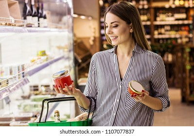 Horizontal shot happy woman reading label with price at caviar jar while standing at seafood supermarket. Beautiful young girl choosing red caviar while doing shopping at grocery shop. Fish appetizer