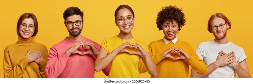 Horizontal shot of happy women and men show heart gesture, express love, say be my valentine, keep hands on chest, feel thankful, isolated on yellow background, confess in truthful feelings.