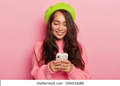 Horizontal shot of happy young brunette Korean woman holds modern mobile phone, sends her photo to boyfriend, reads funny notification, wears green beret and pink loose jumper, poses indoor alone.