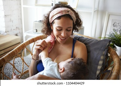 Horizontal shot of happy young mixed race mother with curly hair enjoying intimate moment with her baby son, sitting in weaven chair in bedroom, breastfeeding him, having joyful facial expression