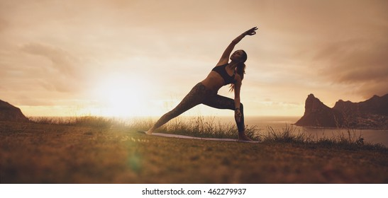 Horizontal shot of healthy female practicing Utthita Parsvakonasana yoga asana. Fitness woman exercising on the cliff during sunset.