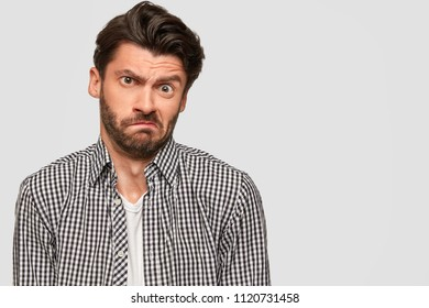 Horizontal shot of hesitant puzzled dispeased male has dark stubble and trendy haitstyle, looks clueless, dressed in checkered shirt, stands against white background with copy space for information