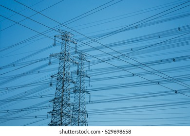 horizontal shot of High-voltage towers silhouetted against blue
