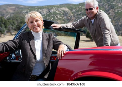 Horizontal shot of a joyous senior couple posing and smiling at the camera in a red convertible on a bright sunny day.
