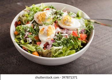 Horizontal shot of large white bowl of Deviled Egg Salad on dark wooden background