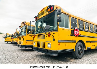 Horizontal shot of a line of parked yellow school buses under a cloudy sky.