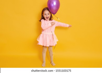 Horizontal shot of little girl with purple balloon isolated over yellow studio background, female child shouting somethig, celebrating herbirtday, kid wearing rosy dress and having dark hair.