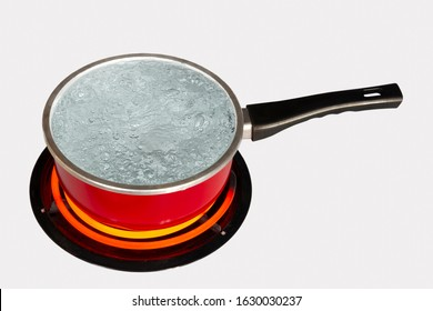 Horizontal shot looking down on a red pot of boiling water on top of a stove with the burner turned to high.  White background.  Copy space.