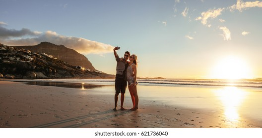 Horizontal shot of loving young couple taking self portrait at the beach. Man and woman on sea shore taking selfie with mobile phone.