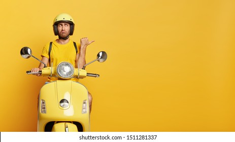 Horizontal shot of man has stubble points away with thumb, shows direction on right side, wears protective headgear and moped, isolated over yellow background. People, transportation concept