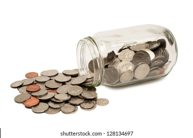 Horizontal shot of many coins spilling out of a glass jar and isolated on a white background with shadow under jar.  Focus is on the center of the coins.