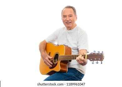 Horizontal shot of a mature man happily playing his guitar on a white background.  Lots of copy space.