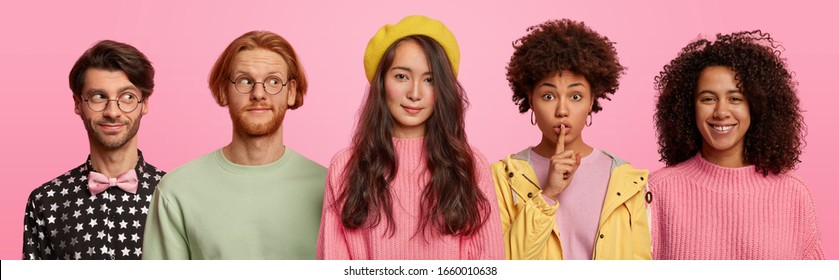 Horizontal shot of mixed young race women and men stand together against pink background, make silence gesture, smile and look gladfully thoughtfully aside, being in good mood. Collage image