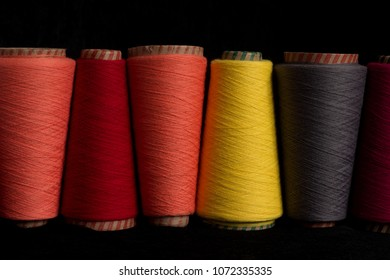 horizontal shot of multicolor sewing threads on black background room for text copy space. Colorful range line of yarn cotton bobbins. Light clothing industry garment apparel.