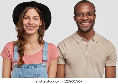 Horizontal shot of multiethnic woman and man stand together against white background, smile broadly, isolated. Satisfied European female farmer in overalls stand next to black man, model in studio