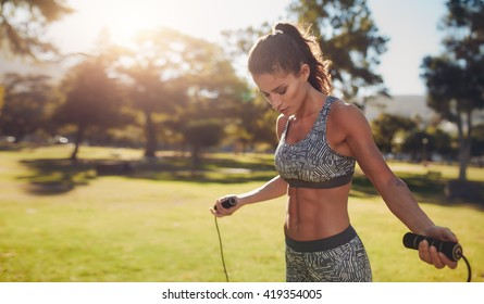 Horizontal shot of muscular woman with skipping rope outdoors in nature. Fitness female doing skipping workout with jump rope in a park on a sunny day.
