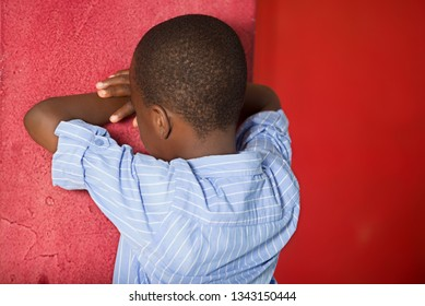 Horizontal shot of an offended child, diverted from camera, stands with his back, face against wall,. A bad-tempered male boy has a difficult character.
