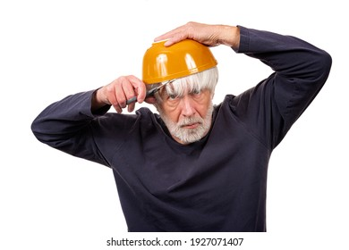 Horizontal shot of an old man giving himself a haircut using a yellow bowl on his head during the pandemic.  White background.