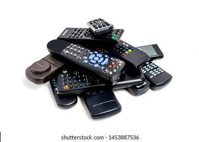 Horizontal shot of a lot of old remote controls piled high. White background.