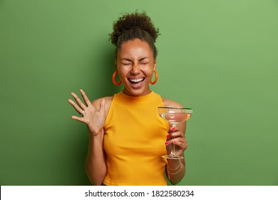 Horizontal shot of overjoyed emotional Afro American curly woman laughs happily and raises palm holds glass of cocktail closes eyes with satisfaction poses indoor against green studio background