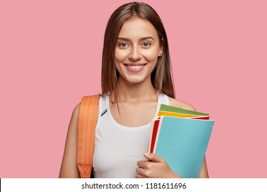 Horizontal shot of pleasant looking cheerful European girl with dark straight hair, dressed in casual white t shirt, carries rucksack and textbooks, isolated over pink background. Emotions, learning
