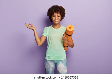 Horizontal shot of pleased dark skinned healthy woman meditates, has yoga exercises, carries fitness mat, shows okay gesture, dressed in sportswear, isolated over purple background. Gymnastic concept