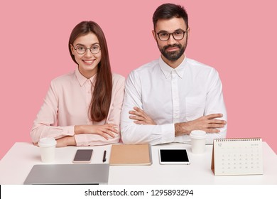 Horizontal shot of pleased self confident professional perfectionists coworkers sit next to each other at workplace, surrounded with modern gadgets, takeaway coffee and calendar, pose over pink wall