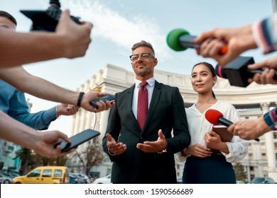 Horizontal shot of politician and his assistant giving interview to journalists. People making interview using equipment set at outdoor location. Selective focus. Front view. Low angle
