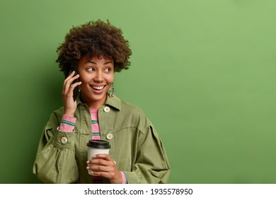 Horizontal shot of pretty Afro American woman has telephone conversation keeps smartphone near ear drinks takeaway coffee looks away with gentle smile isolated over green background copy space