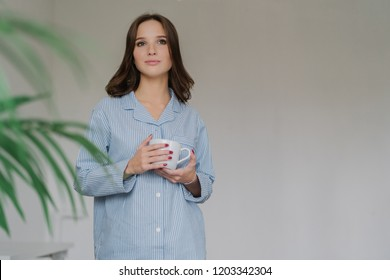 Horizontal shot of pretty woman dressed in oversized striped shit, has attractive loo, holds cup of coffee or latte, stands indoor with blank copy space on left for your advertising content or text