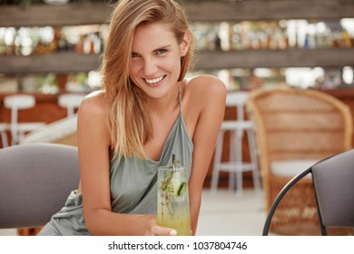Horizontal shot of pretty young blonde woman dressed in casual clothing, recreats against cozy cafe inyerior with fresh cold coktail, smiles happily into camera. Cheerful adorable female in bar