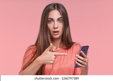 Horizontal shot of pretty young female with long hair looks with bugged eyes, holds modern smart phone, recieves unexpcted message from friend, reads reminder, isolated over pink background.