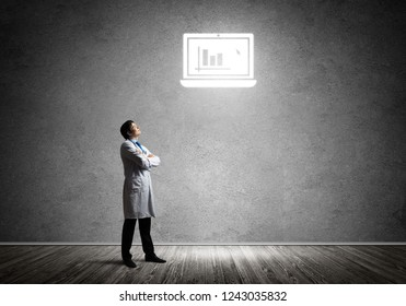 Horizontal shot of professional and confident doctor in white medical suit interracting with glowing computer icon against gray dark wall on background
