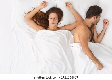 Horizontal shot of relaxed married woman and man stay in bed together, enjoy cozy morning and intimacy, have healthy sleep, rest after passionate sex, lie under white sheets. Good night sleep