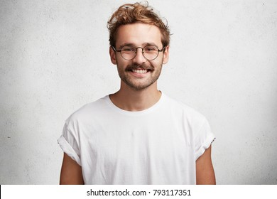 Horizontal shot of satisfied content bearded male wonk has happy smile on face, glad to achieve great results and get award for his work, dressed casually, isolated over white concrete wall.