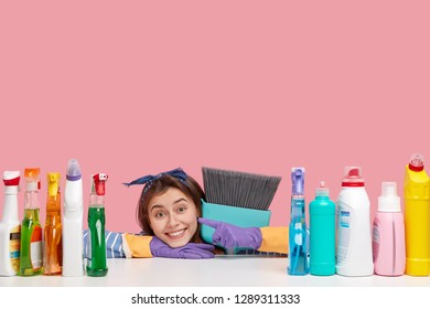 Horizontal shot of satisfied housemaid wears headband, points at detergents, carries broom closely, likes its perfect effect, delighted after cleaning all rooms in house, isolated on pink wall