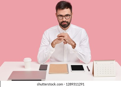 Horizontal shot of self assured handsome bearded young man in white formal shirt, wears transparent glasses, sits at desktop, being perfectionist, neat workplace, isolated over pink background.