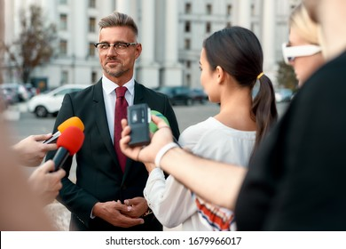 Horizontal shot of serious politician looking away and giving interview to reporters. People making interview using microphones and equipment set at outdoor location. Selective focus. Front view