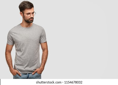 Horizontal shot of serious unshaven male in casual grey t shirt, keeps hands in pockets, looks aside, thinks about something, poses over white wall with free space for your advertisement or promotion