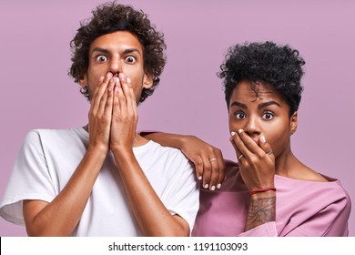 Horizontal shot of shocked African American young female and male look with scared frightened expressions at camera, cover mouth, being stunned to recieve bill, have no money for paying debts.