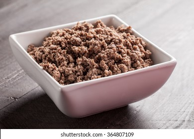 Horizontal shot of small white bowl of cooked ground meat on brown wooden table