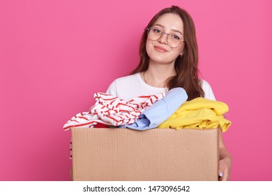 Horizontal shot of smiling female posing isolated over pink background and holding box with rausable clothes, clothing for children`s home or poor people, charming girl woman making charity.
