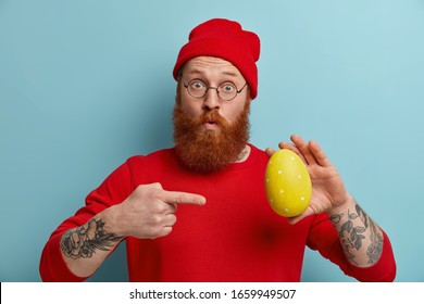 Horizontal shot of surprised man has thick ginger beard, points at big yellow decorated Easter egg, demonstratess his ability to draw and decorate, looks with wonder at camera. People, holiday