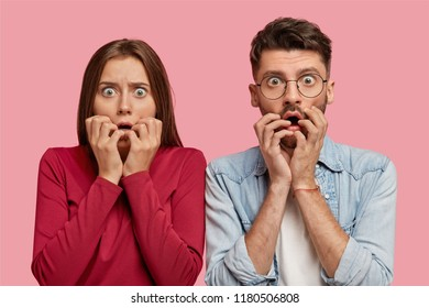 Horizontal shot of terrified young female and male youngsters watch horror film together, keep hands near mouth, have frightened expressions, isolated over pink background. Omg, its horrible!