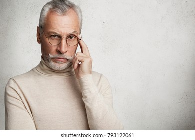 Horizontal shot of thoughtful pensive elderly bearded male keeps finger on temple, contemplates about something important, isolated over blank copy space for your advertising content or text
