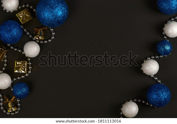 Horizontal shot of three blue balls and three decorative snowballs and beads at left and right on black background. Top view with copy space for text