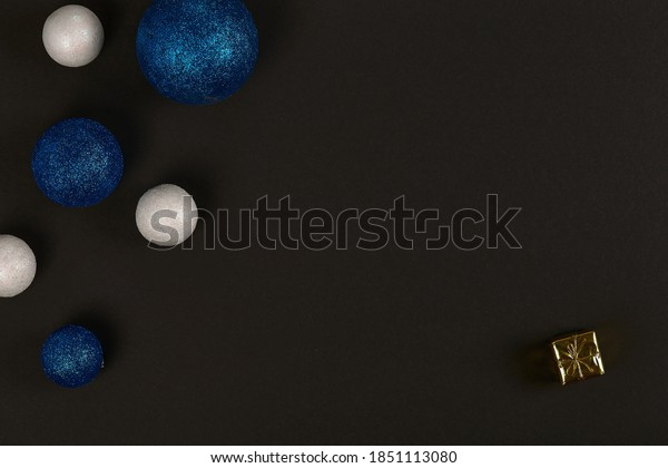 Horizontal shot of three blue balls and three decorative snowballs at left and present at right down corner. on white background. Top view with copy space for text