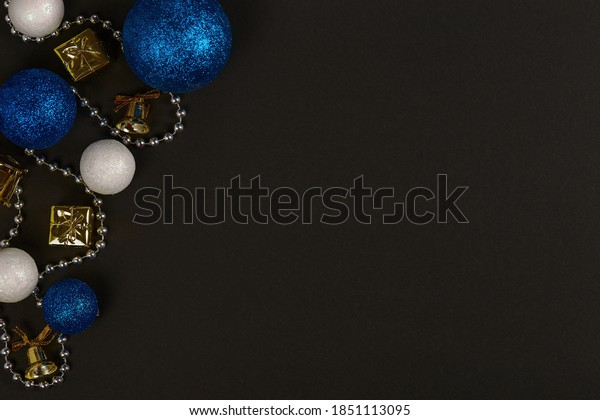 Horizontal shot of three blue balls and three decorative snowballs and beads at left on black background. Top view with copy space for text
