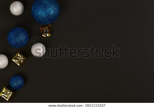 Horizontal shot of three blue balls and three decorative snowballs and gold present and bell at left. on black background. Top view with copy space for text